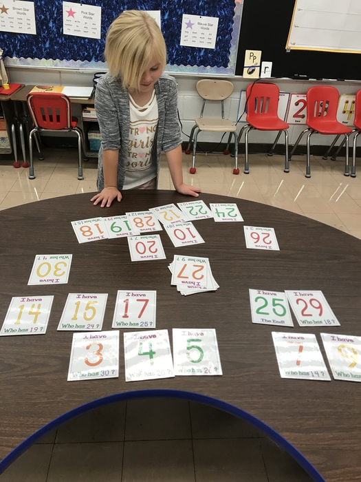 First grade working on number identification with 'I Have, Who Has'